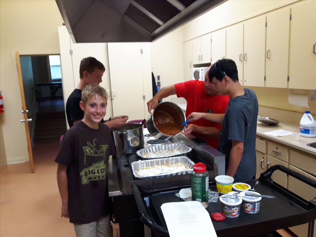 Scouts practicing their cooking skills by preparing a meal for ARK Outreach Centre.